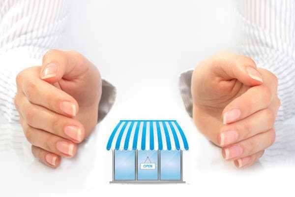 Mãos segurando uma pequena loja